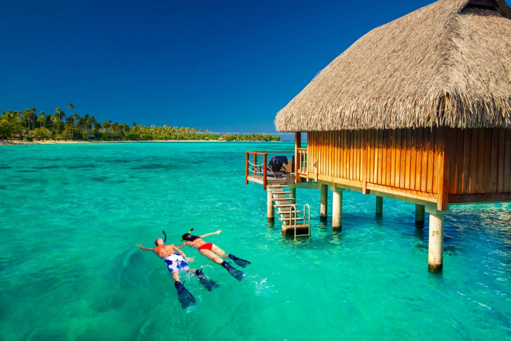 Picture of couple snorkeling by their idyllic water villa.